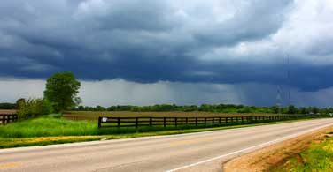 Pictured: An overcast cloudy sky behind a road in Springfield Illinois.
