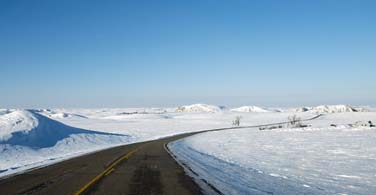 Pictured: A road with a snowy surrounding in Bismarck North Dakota.