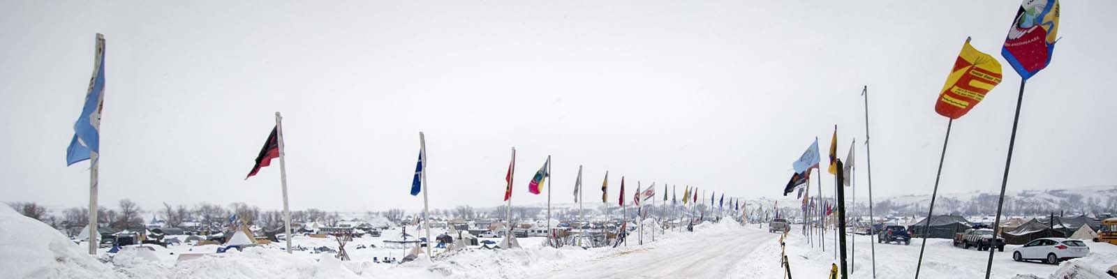 PIctured: A snowy road with flags in North Dakota.