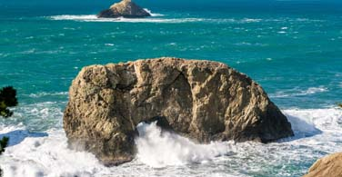 Large rock with waves crashing in the ocean