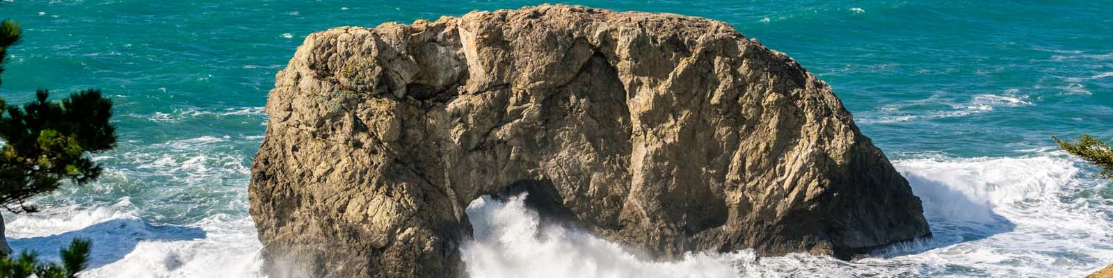 Pictured: Large rock in the sea with waves in Oregon.