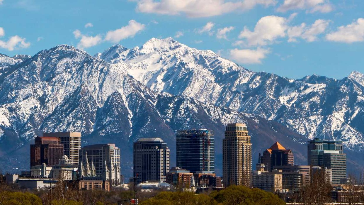 This is a skyline image of downtown Salt Lake City with mountains in the background.