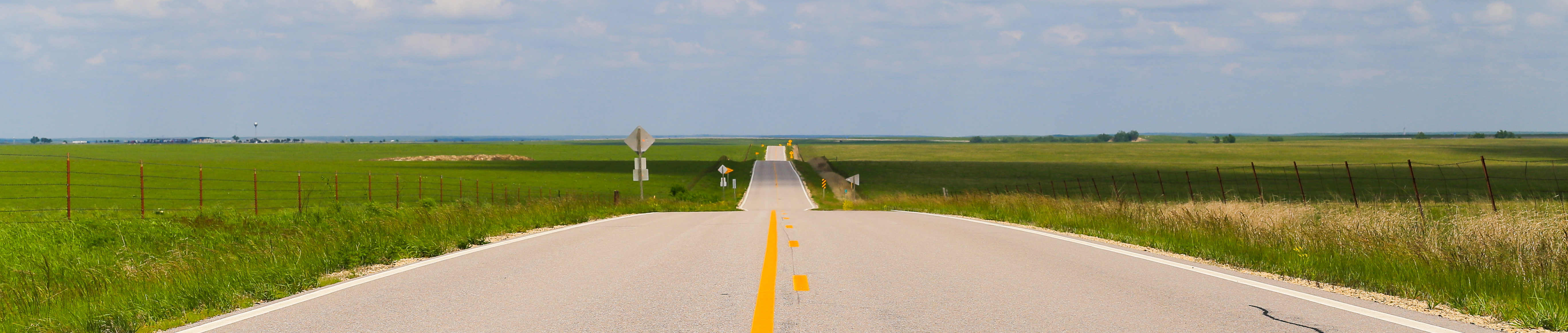 Pictured: Kansas road in the plains with green grass.