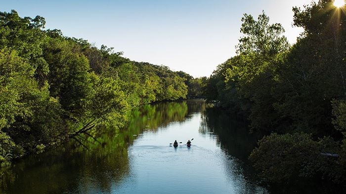 This is an image of a river and two people in kayaks in Springfield Missouri.