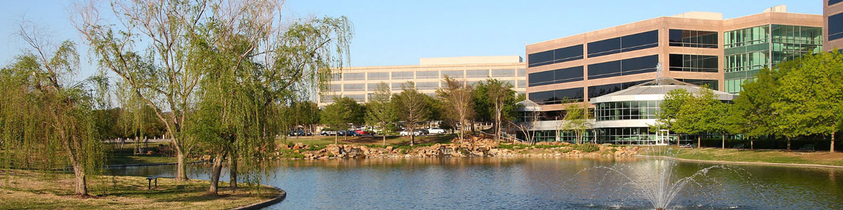 This is an image of commercial buildings across a lake in Plano. ASTA-USA provides translation services in this city.